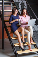 A girl and her, sitting on the stairs, working behind a laptop