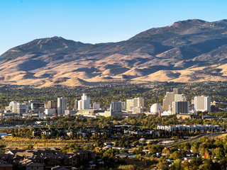 City of Reno Nevada cityscape with casinos, hotels, apartments, housing, roads and the Sierra Nevada Mountains in the background.