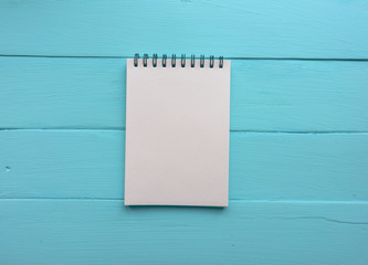 Notebook with a spring. Bright blue, turquoise surface. Painted Board. Close-up with copy space. Top view