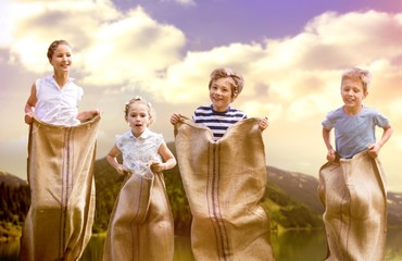 Composite image of friends playing sack race