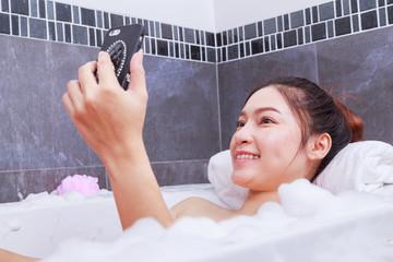 woman making selfie photo in bathtub in bathroom