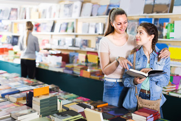 Young female with daughter are choosing books