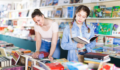 smiling happy woman showing open book to girl in book boutique