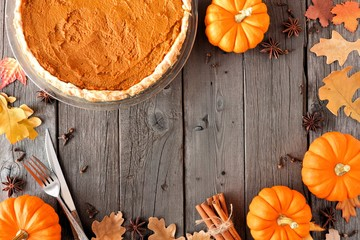 Autumn table scene frame with pumpkin pie, pumpkins, leaves and spices over a wood background