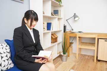 woman in suit reading a book