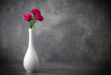 artificial flowers in white vase with background of concrete