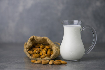 almond milk in jar with almonds in sackcloth on concrete background