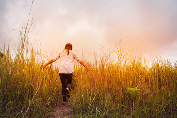 a woman walking in the  grass field with happy