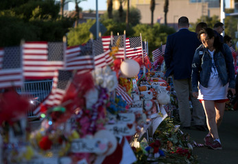 """Terri Xiang of Texas looks over 58 wood crosses, with the names and photos of the October 1 mass shooting victims, in the median of Las Vegas Boulevard South near the """"Welcome to Las Vegas"""" sign in Las Vegas"""