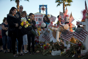 """Samantha Langton, 10, places flowers at 58 wood crosses, with the names and photos of the October 1 mass shooting victims, in the median of Las Vegas Boulevard South near the """"Welcome to Las Vegas"""" sign in Las Vegas"""