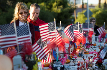 """A couple looks over 58 wood crosses, with the names and photos of the October 1 mass shooting victims, in the median of Las Vegas Boulevard South near the """"Welcome to Las Vegas"""" sign in Las Vegas"""