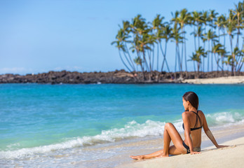 Bikini girl lying on sand sun tanning in Hawaii. Travel vacation woman relaxing on tropical nature relaxing landscape. Young person enjoying ocean view.