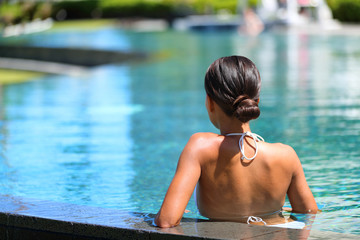 Wellness spa relaxation luxury pool resort young woman enjoying swimming in water at tropical holiday destination.