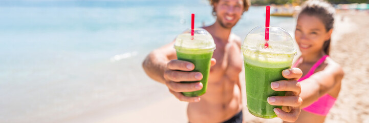 Fitness couple drinking green smoothie at beach banner panoramic. Man and woman holding vegetable smoothies after running sport fitness training. Healthy clean eating lifestyle concept.