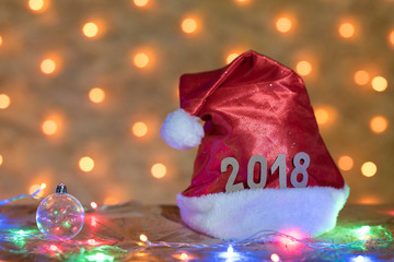 Red cap with figures of 2018 on a table on the background of a New Year's garland with blurred golden lights