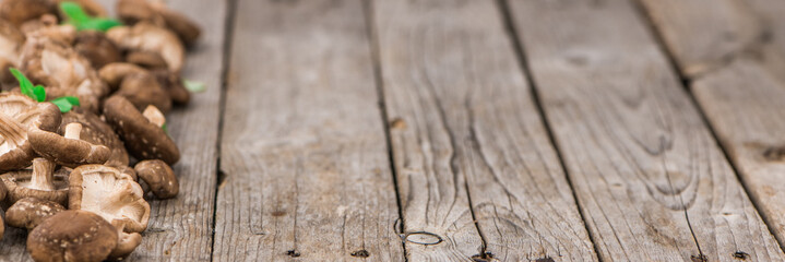 Portion of Raw Shiitake mushrooms on wooden background, selective focus