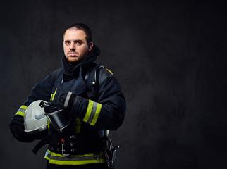 Firefighter dressed in uniform holds safety helmet.