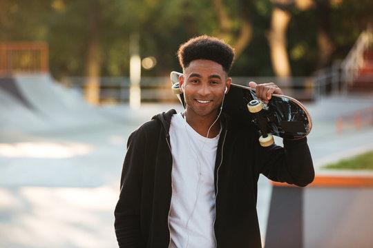 Cheerful african teenager guy with earphones