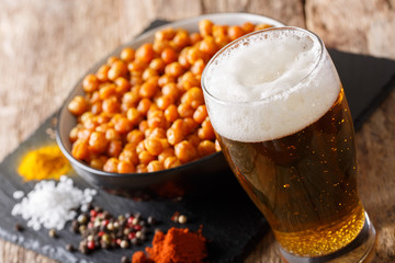 glass of light beer with a snack roasted salted chickpeas close-up. horizontal