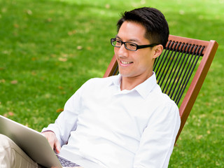 Young businessman using laptop while sitting outdoors