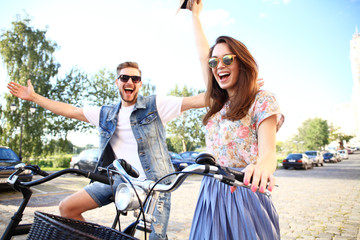 Happy young couple going for a bike ride on a summer day in the city.They are having fun together.