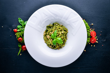 """Pasta with pine nuts and greens. Plate with the word """"paste"""". Top view. Free space for text. On a wooden background."""