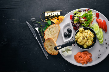 English breakfast. Fried eggs, salmon, olives, nuts, vegetables and dried fruit. Top view. Free space for text. On a wooden background.