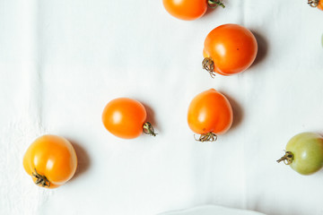 Fresh organic tomatoes of different colors on white textile background. Harvest concept. Horizontal composition. Overhead view, natural lighting, copy space.