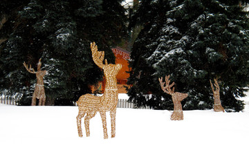 Glowing Christmas figures deer standing near fir-tree on snow in blizzard