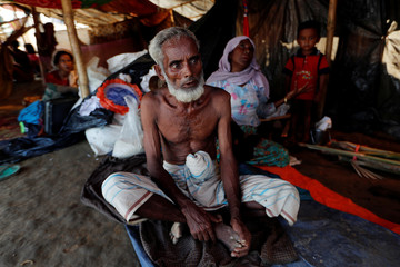 A Rohingya refugee family is seen in their shelter, in a camp near Cox's Bazaar