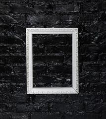 white elegant frame on a black brick wall