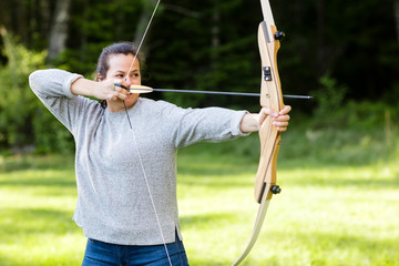 Female Archer Aiming With Bow And Arrow In Forest