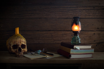 Lantern light on books and Skull with candle extinguish on head all  is on the wooden plank
