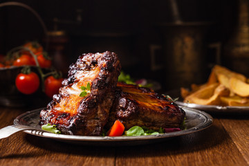 Roasted ribs, served on an old plate. Dark or balck background.