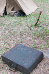 old shovel and war briefcase in front of a military tent