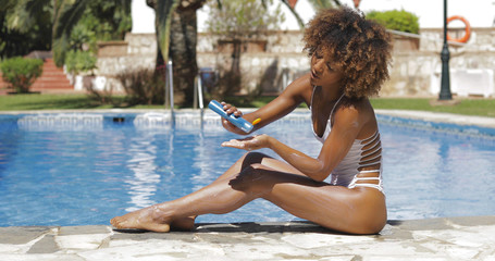 Side view of curly ethnic woman in white swimsuit posing on poolside and applying protective lotion on skin while sunbathing.