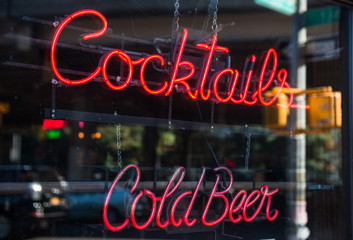 Cocktails and cold beer neon sign in the window of a bar