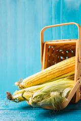 Photo of corn cobs in wooden basket
