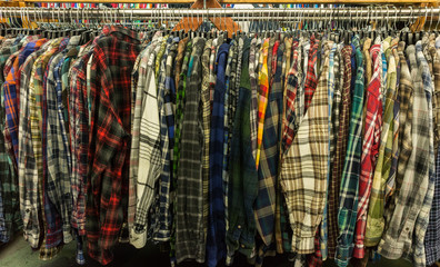Used flannel shirts hanging on a clothing rail in a thrift store