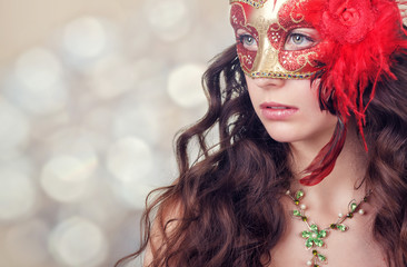 Beautiful young woman in a red carnival mask on a background of holiday lights.