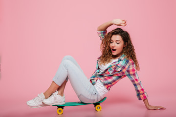 Young lady posing on skateboard idolated over pink