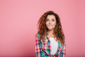 Young lady blowing bubble gum isolated over pink