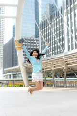 lifestyle asian business woman feel happy jumping in air celebrating  success and achievement  on business district ,  business concept.