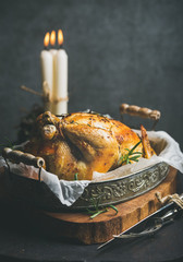 Christmas table set with oven roasted whole chicken with oranges, bulgur and rosemary, decorative candles on wooden board, grey concrete wall background. Selective focus, copy space, Slow food concept
