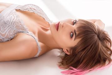 woman in lace bralette lying on floor