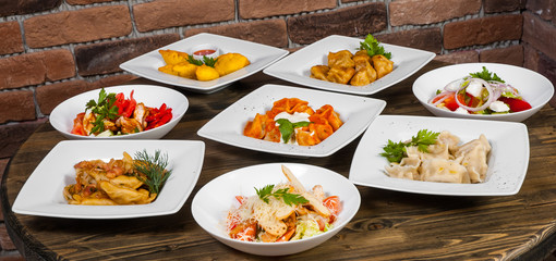 Set of different salads, dumplings and ravioli on a wooden table