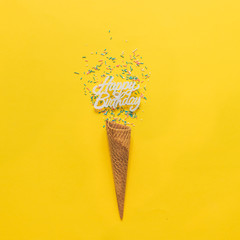 an ice cream cone, happy birthday inscription and confetti on yellow background