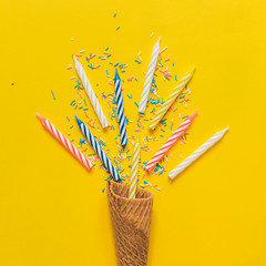 an ice cream cone, birthday candles and confetti on yellow background