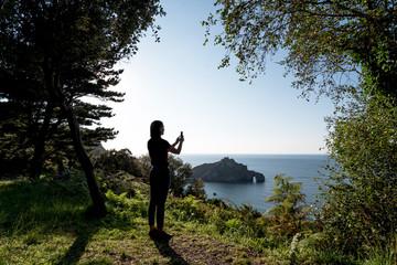 Silhouette of young woman taking photos of Hermitage San Juan de Gaztelugatxe