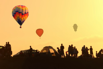 Hot air colorful balloons flying in the sky at sunrise. Silhouettes of people watching the flight from the ground